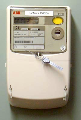 Panel-mounted solid state electricity meter, connected to a 2 MVA electricity substation. Remote current and voltage sensors can be read and programmed remotely by modem and locally by infra-red. The circle with two dots is the infra-red port. Tamper-evident seals can be seen