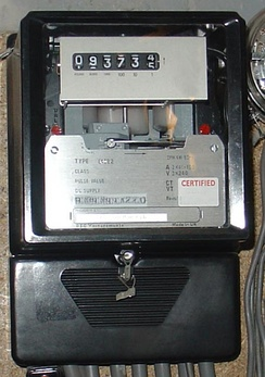 Three-phase electromechanical induction meter, metering 100 A 240/415 V supply. Horizontal aluminium rotor disc is visible in centre of meter